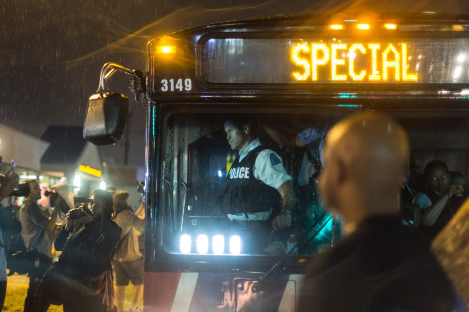 A police officer stares at protesters from a metro bus waiting for the state imposed curfew to start on August 17, 2014.