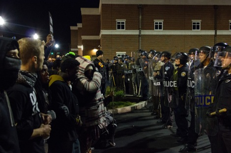 Police and protesters stand face to face in the parking lot of the Ferguson Police Department.