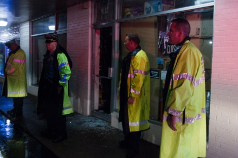 Police guard a looted business in Ferguson, MO on the anniversary weekend of Michael Brown's death.
