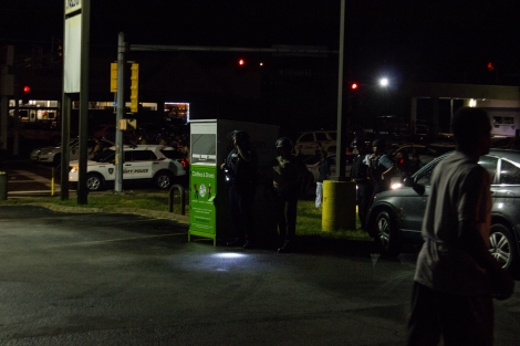Police officers take cover after gunfire is exchanged at a protest in Ferguson, MO.