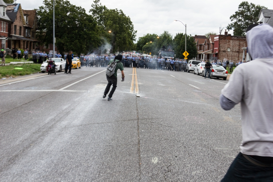 A protester reaching to throw back a tear gas can police shot at protesters in St. Louis, MO.