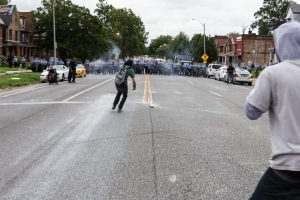 A protester runs towards tear gas to throw back at police.