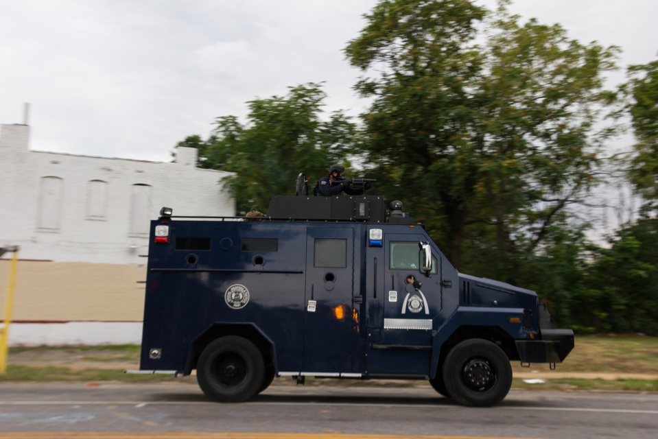 Police with grenade launchers drive down Page Blvd. in St. louis, launching tear gas to disperse protesters from the area that Mansur Ball-Bey was killed by police.
