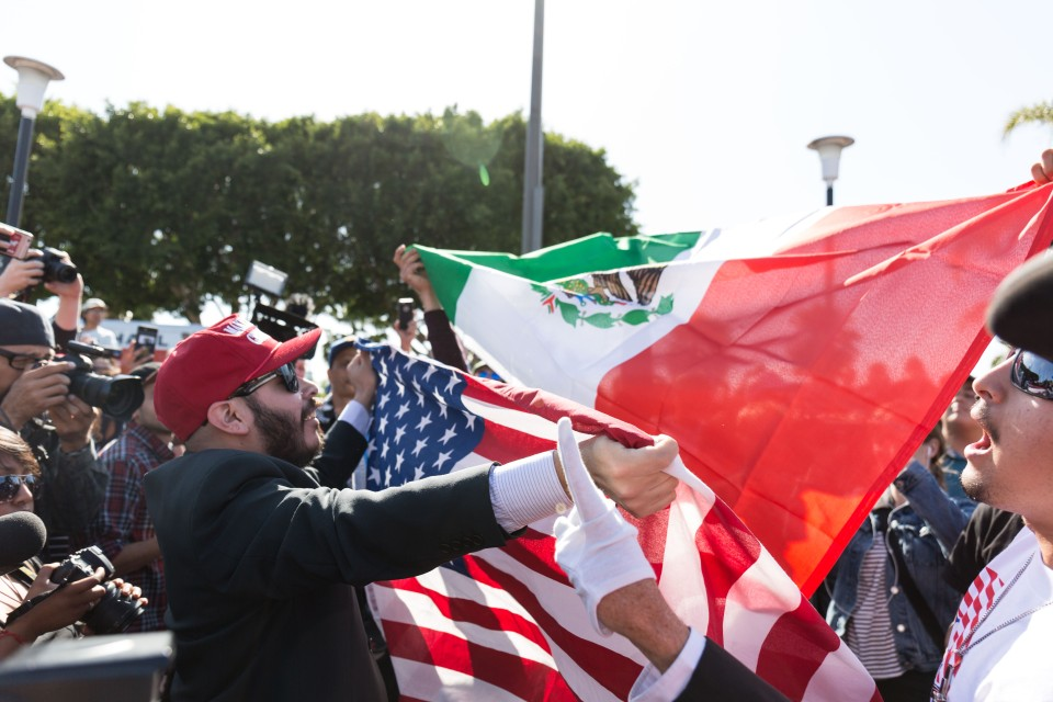 A Trump supporter blocks a protester holding a Mexican flag with and American flag at the trump rally in Costa Mesa, CA.