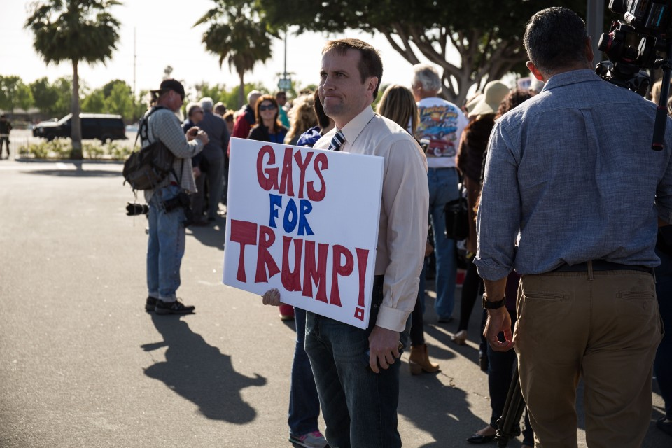A man holds a sign that says Gays for Trump outside the trump rally in Costa Mesa, CA.