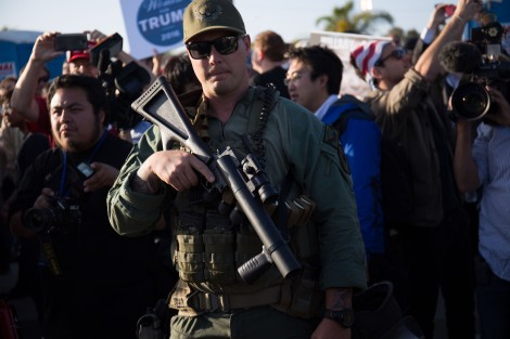 A police officer standing between Trump supporters and protesters carries a less lethal gun for crowd control.