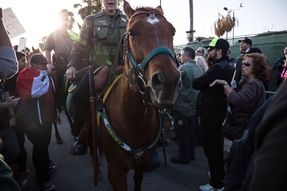 Mounted police push through the crowd of Trump protesters and supporters in Costa Mesa, CA.