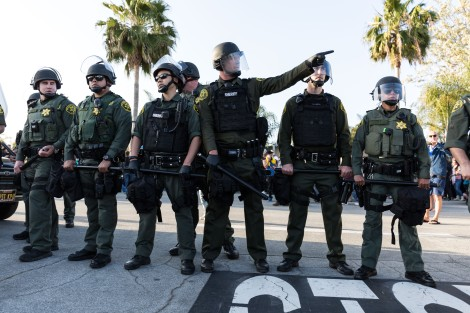 Police in riot gear are directing protesters away from Tump supporters outside the Trump rally in Costa Mesa, CA.