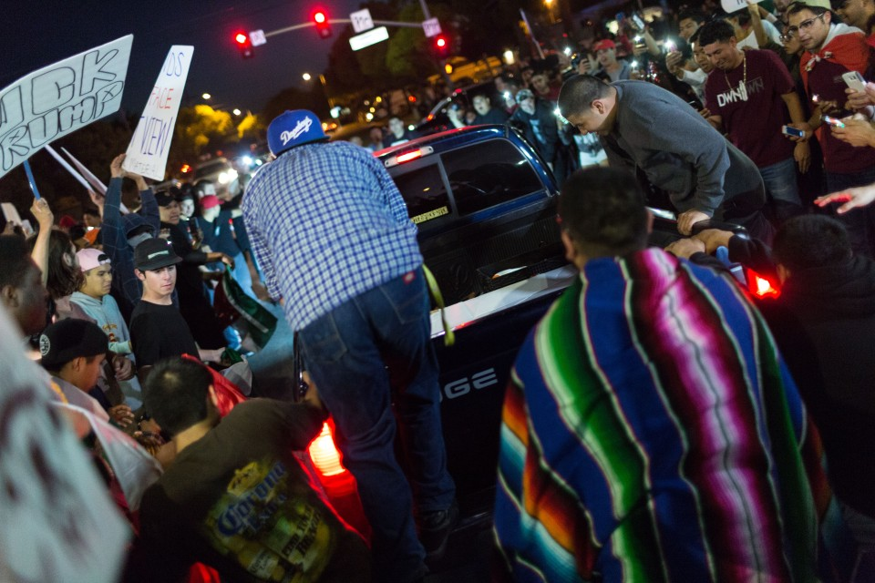 Protesters stand on the back of a truck as it burns out at the intersection of Fair and Fairgrounds in Costa Mesa, CA.