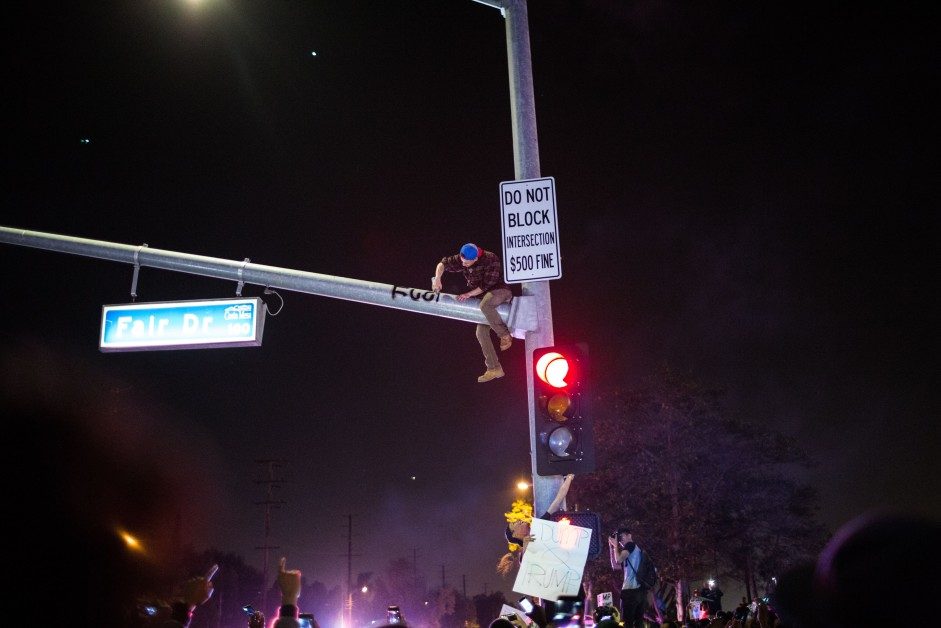 A man climbs a traffic light and writes anti trump graffiti on it.