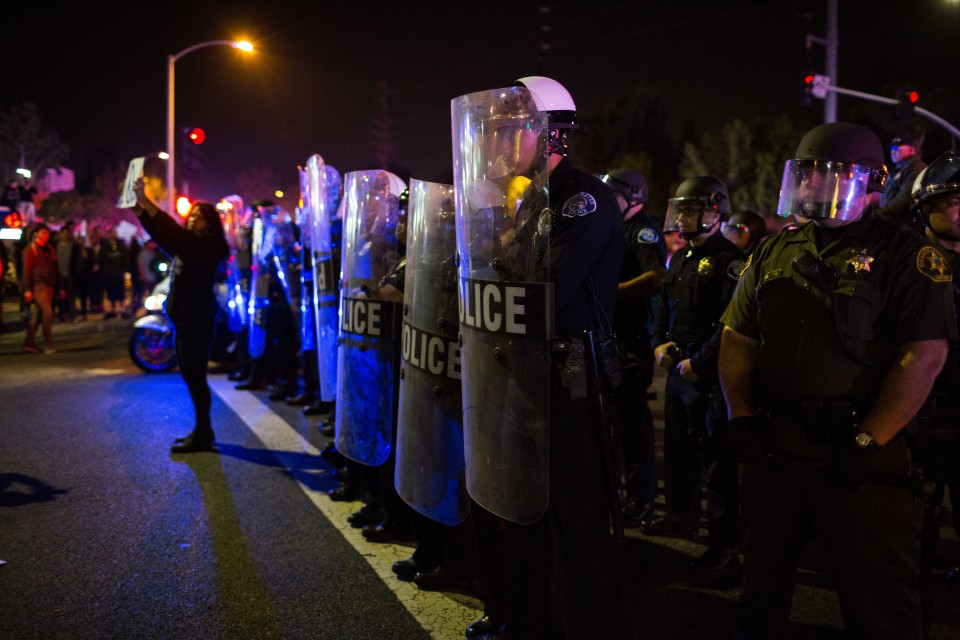 Riot police move the protesters out of the intersection outside the Donald Trump rally in Costa Mesa, CA.