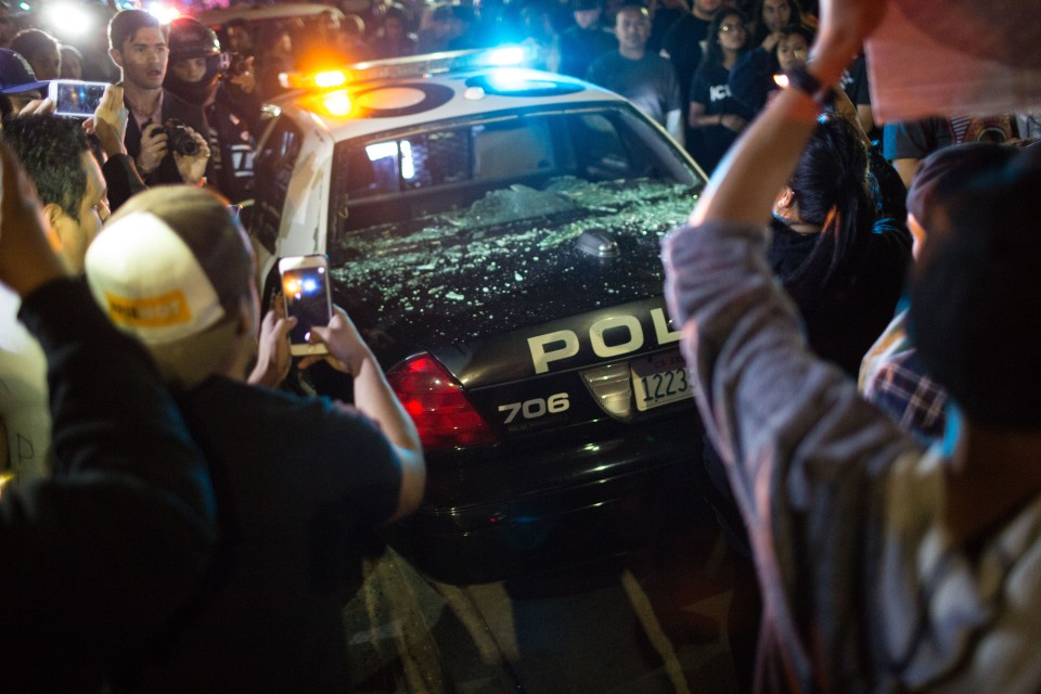A police car has its windows smashed outside the Donald Trump rally in Costa Mesa, CA.