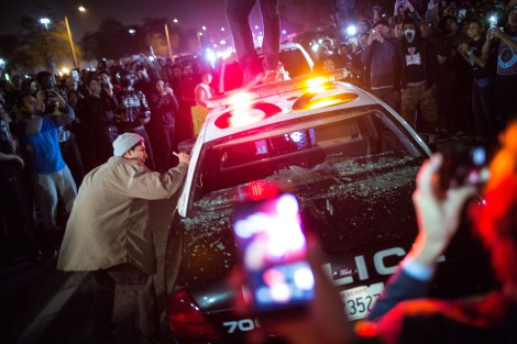 A protesters jumps on top of a police car after its windows have been broken at the Trump rally in Costa Mesa, CA.