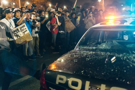 A protester kicks a cop car after its windows are smashed out outside the Donald Trump rally in Costa Mesa, CA.