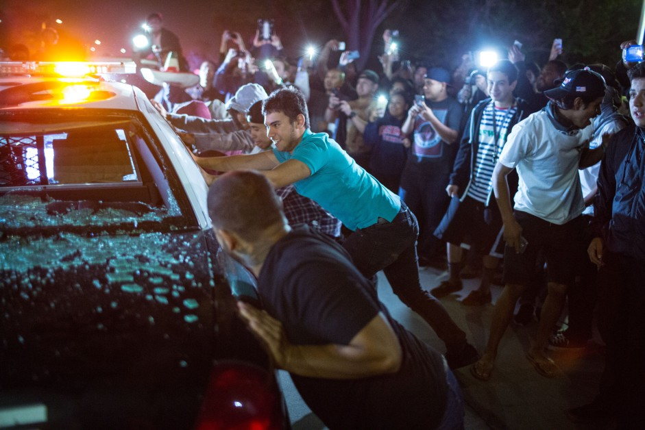 Protesters attempt to turn over a police car outside the Tump rally in Costa Mesa, CA.
