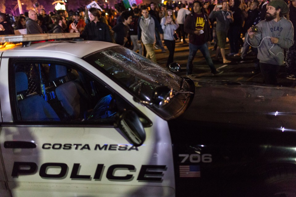 A police car has its windshield smashed outside the Donald Trump rally in Costa Mesa, CA.