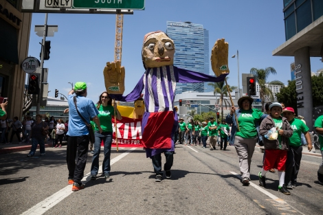 """Koreatown Immigrant Workers Alliance (KIWA) march with giant puppets for International Workers"""" Day."""