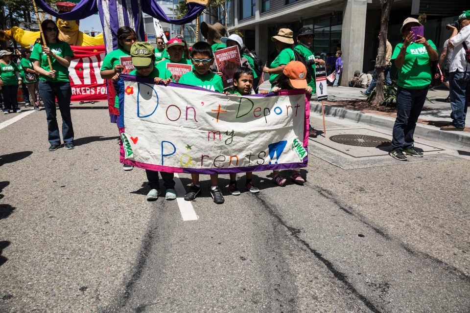 Four children hold up a banner saying Don't Deport my Parents at the International Workers' Day march