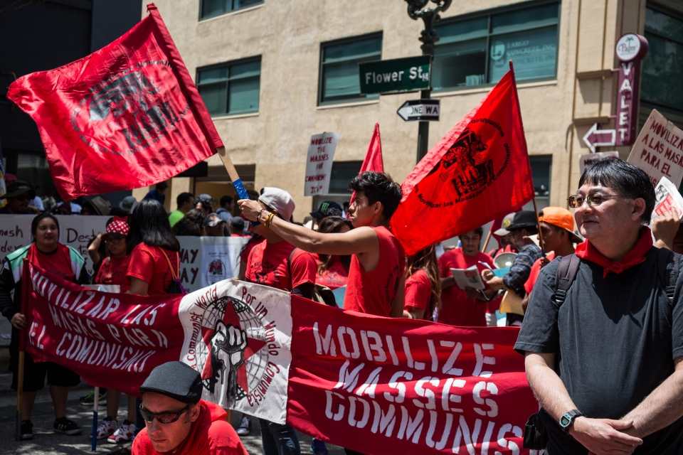 A communist group waves red flags waiting for the march to start.