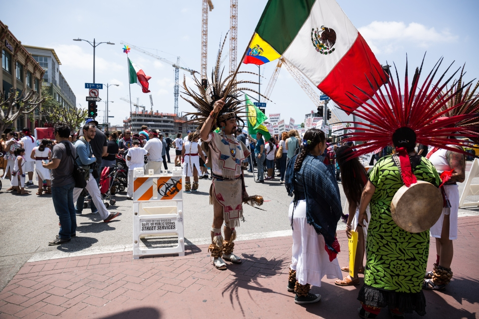 A protester representing indigenous people waves a Mexican flag before the march starts.