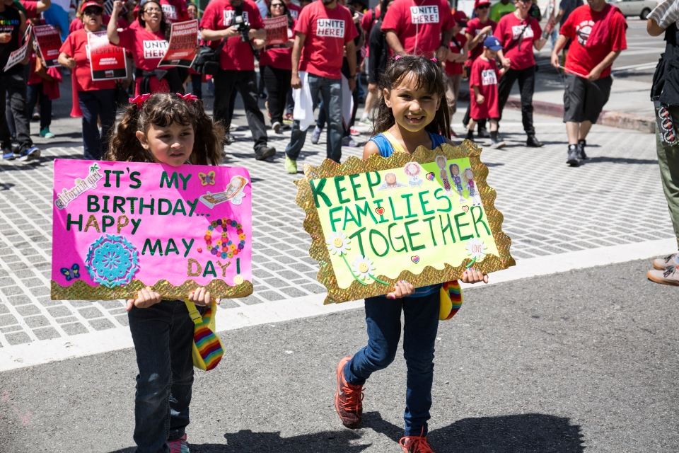 Two kids with signs march with protesters for International Workers' Day in Downtown Los Angeles.