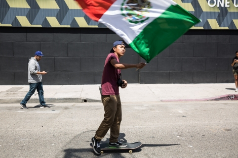 A man flies a Mexican flag while skateboarding in the march in Downtown Los Angeles.
