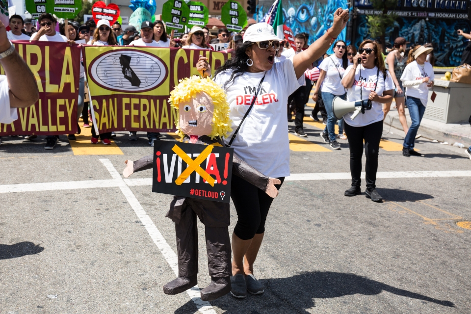 A woman carries a Donald Trump piñata in the International Workers' Day march.