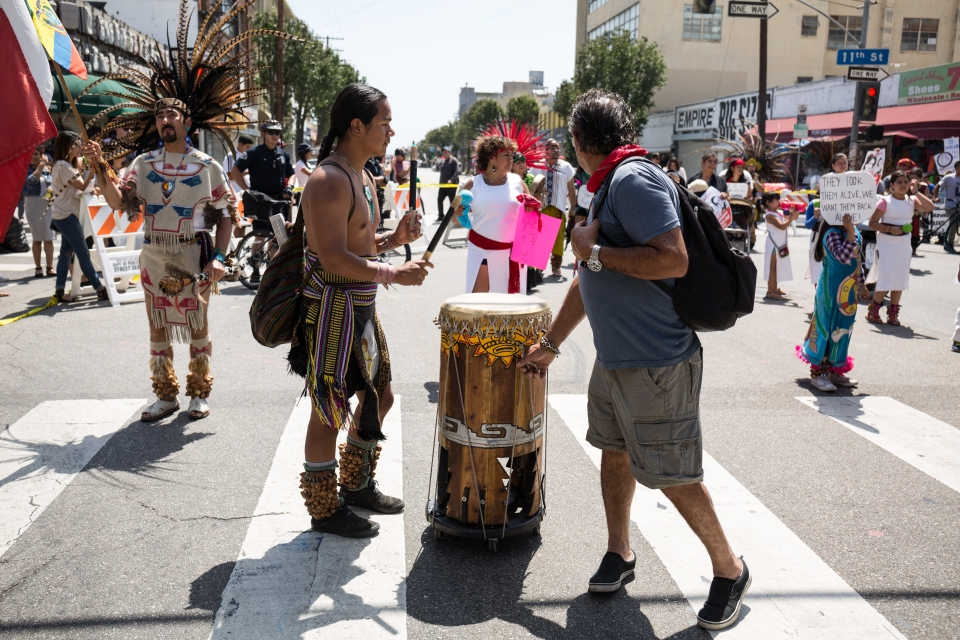 A protester representing indigenous people plays a drum during the march.