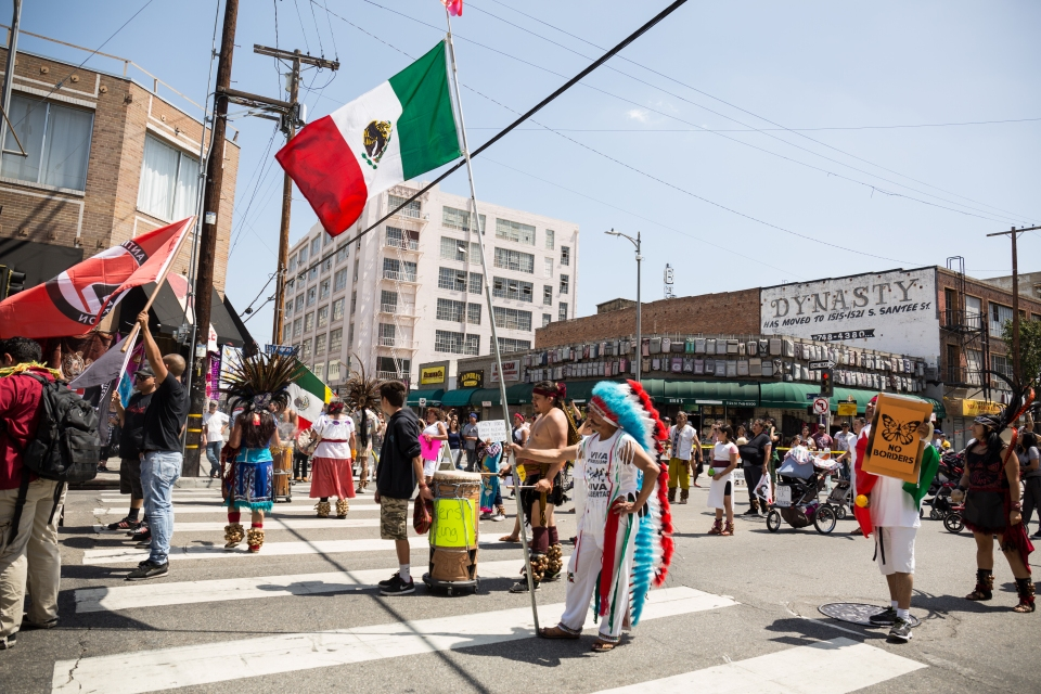 A protester representing indigenous people holds up a Mexican flag during the march.