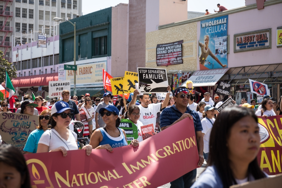 Pro immigration protesters hold signs in the International Workers' Day march.
