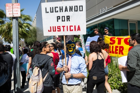 A protester wears a luchador mask at the Los Angeles Metropolitan Detention Center while the march is stopped.