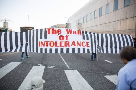 A large banner made of paper that represents the United States and Mexico border fence that says The Wall of Intolerance stops the march in front of the Metropolitan Detention Center in Downtown Los Angeles.