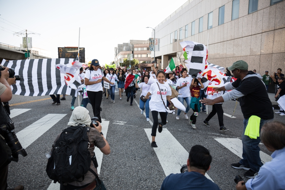 Children run through the banner representing the United States and Mexico border fence in front of the Metropolitan Detention Center in Downtown Los Angeles.