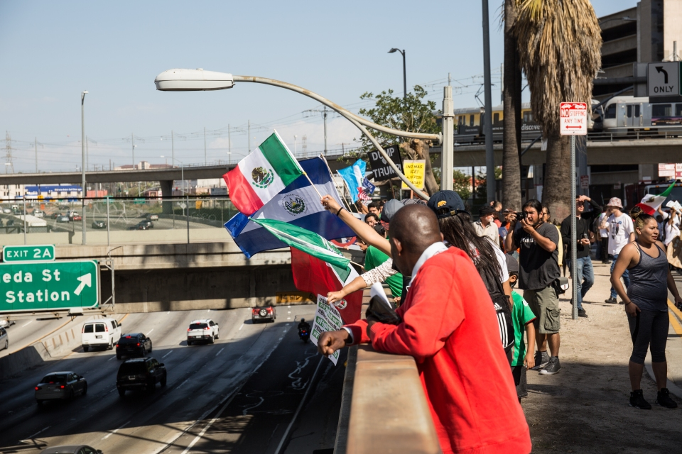 Protesters hold flags and banners over a freeway at the end of the march route.