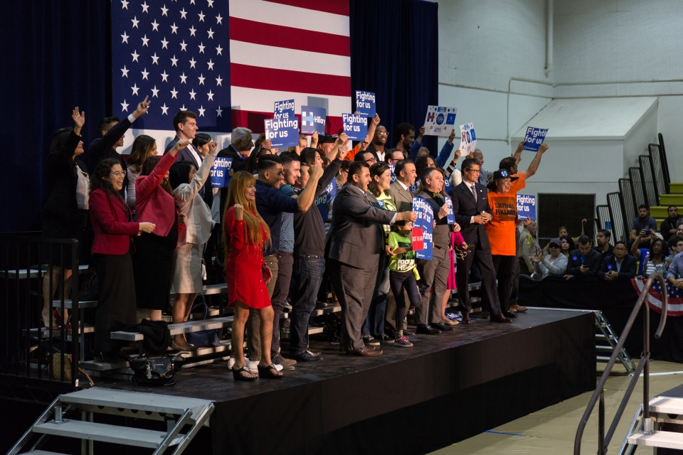 "An energetic crowd holding signs that read ""Fighting for Us"", stands on a stage behind the podium where Hillary Clinton is going to speak at East Los Angeles College on May 5, 2016."