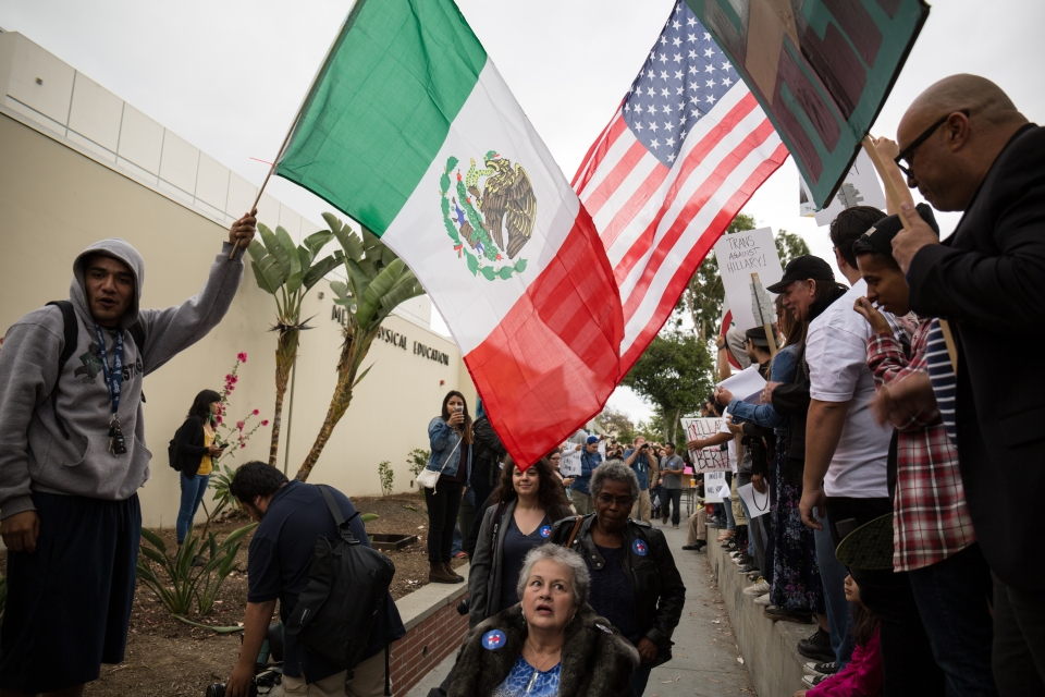 Protesters hold a Mexican and an American flag that people leaving the event at East Los Angeles College had to pass under. May 5, 2016