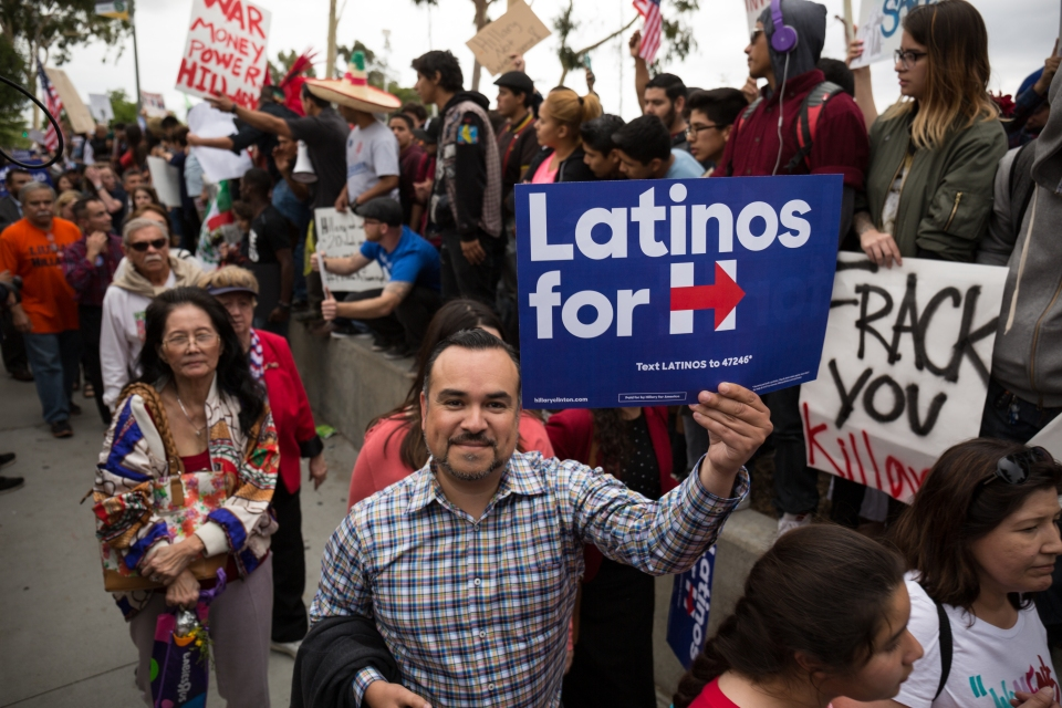 A man holds a Latinos for Hillary sign as he walks through the line of protesters outside of the Clinton event at East Los Angeles College on May 5, 2016.